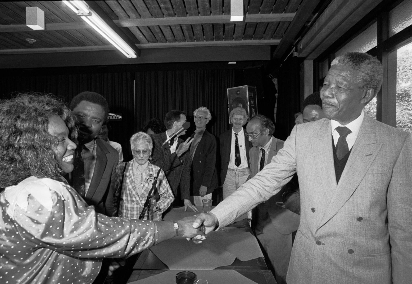 Nelson Mandela geeft een hand aan een vrouw.